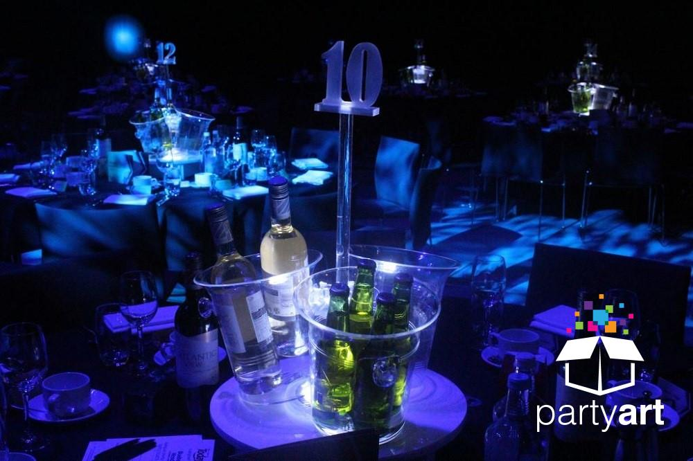 A customised lit table centre with a table number alongside it.